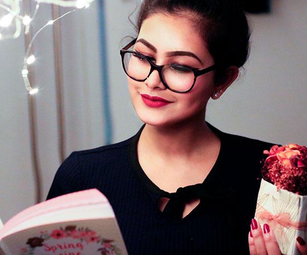 mujer-feliz-con-gafas-leyendo-libro-y-sosteniendo-flores