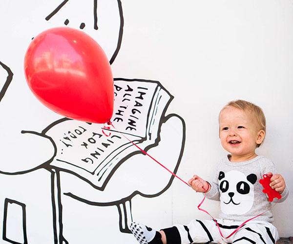niño-bebe-sentadao-con-globo-rojo-frente-a-pared-con-dibujo